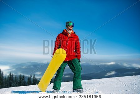 Snowboarder in glasses poses with board in hands
