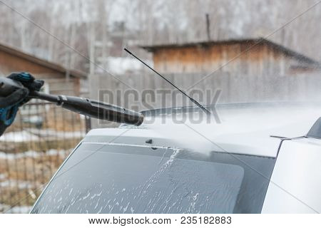 Car Wash. Wash The Car With High Water Pressure. High Water Pressure On The Car. A Man Washes A Car