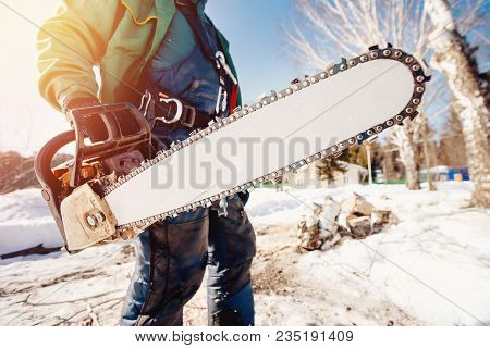 Chainsaw. Close-up Of Man Lumberjack Holding Chainsaw For Cutting Down Trees.