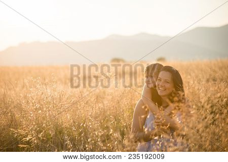 Carefree Young Mom Having Fun With Her Daughter In The Field