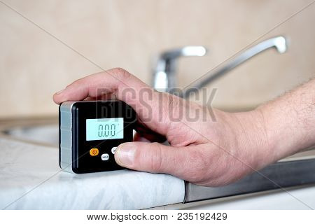 Man Using A Small Digital Spirit Level To Check Level Of Kitchen Sink Table At Home.