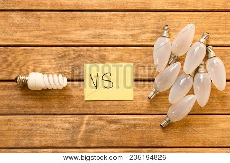 Energy-saving Lamp Vs. Incandescent Lamp . The Concept Of Energy Saving . On A Wooden Table .