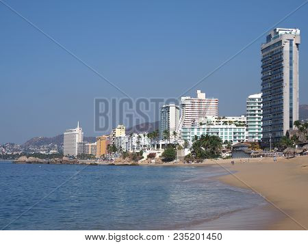 Scenic Sandy Beach Panorama At Bay Of Acapulco City In Mexico With White Hotels Buildings And Skyscr