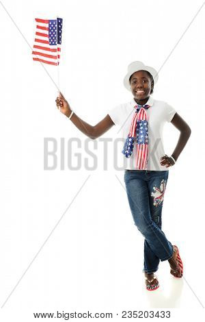 A happy American tween holding a flag while proundly wearing her stars and stripes. On a white background.