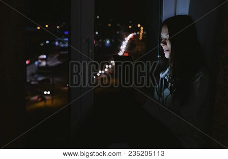 Happy Woman Using Tablet For Video Chatting. Sitting On The Windowsill In The Dark Night. Road With
