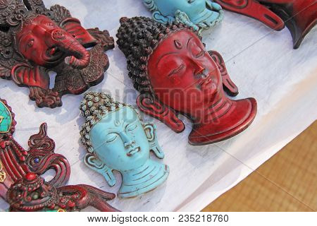 The Red Face Of The Buddha Is The Blue Ganesha In The Market Of The Bazaar In India. Figures Of Budd