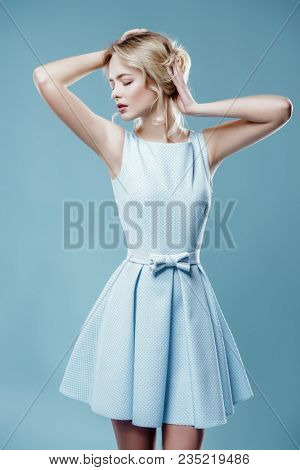 Beauty, fashion shot. Beautiful young woman with hairstyle and make-up posing in elegant blue dress. Studio shot.