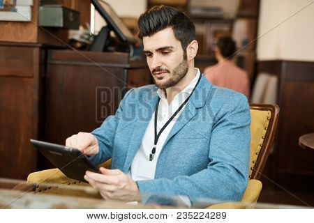 Handsome young businessman sitting at cafe, using tablet computer.