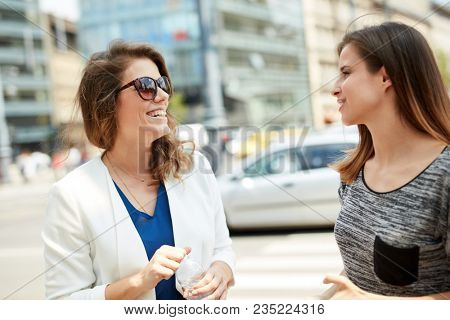 Young women talking in the city outdoors at springtime.