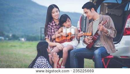 Happy Little Girl Playing Ukulele With Asian Family Sitting In The Car For Enjoying Road Trip And Su