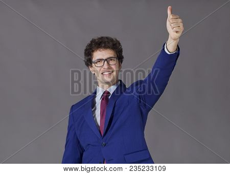 A Boy With Blue Jacket And Necktie Showing Big Thumb Up