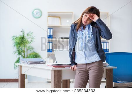 Pregnant woman struggling to do work in office