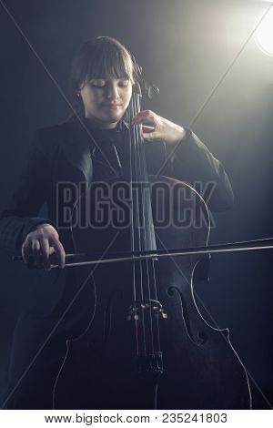 Cellist Playing Classical Music On Cello Against A Black Background