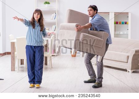 Man moving armchair in the living room