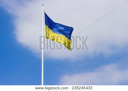 National Flag Of Ukraine Of Blue And Yellow Colors Flying In The Wind On The Flagpole On A Backgroun