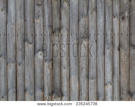A Fence Made From Brown Round Vertical Pine Logs. Natural Log Background