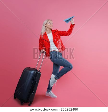 Concept, Ready To Travel. Happy Young Woman With Travel Suitcase Launches Paper Airplane. Blonde Tou