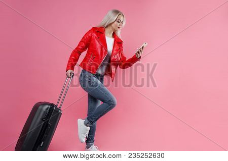 Concept To Hurry To The Airport. Young Woman With Suitcase On Pink Background. Smartphone In Hand, C