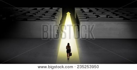 Woman going straight ahead on a lighted carpet arrow between two maze