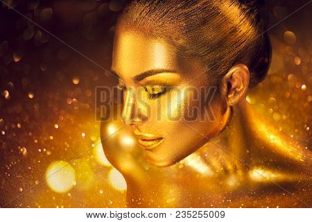 Fashion art Golden skin Woman face portrait closeup. Gold jewellery, jewelry, accessories. Beauty gold eyes, Lips, Skin and hair. Model girl with holiday golden Glamour shiny professional makeup