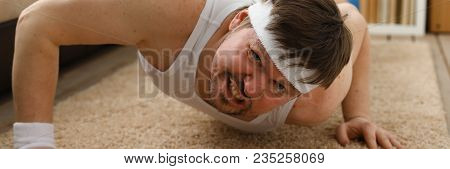 A Young Handsome Man With Excess Weight Makes The First Fitness Training At Home On The Carpet Is Wr