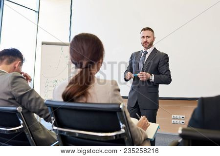 Portrait Of Bearded Business Coach Standing By Whiteboard Giving Presentation For Audience, Copy Spa