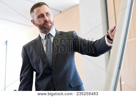 Waist Up Portrait Of Bearded Business Coach Standing By Whiteboard Giving Presentation