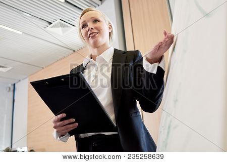 Low Angle Portrait Of Blonde Businesswoman Standing At Whiteboard Giving Presentation To Audience