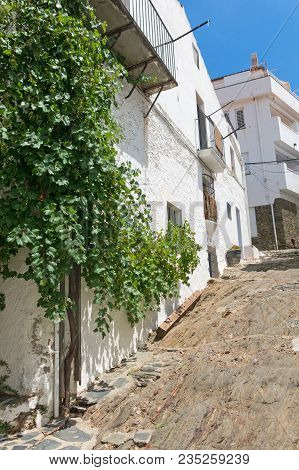 Typical White And Narrow Mediterranean Street, In The Small Fishing Village Of Cadaques, Typical Med