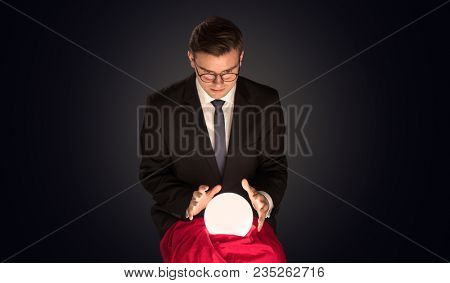 Handsome businessman with magic ball and copy space and dark background