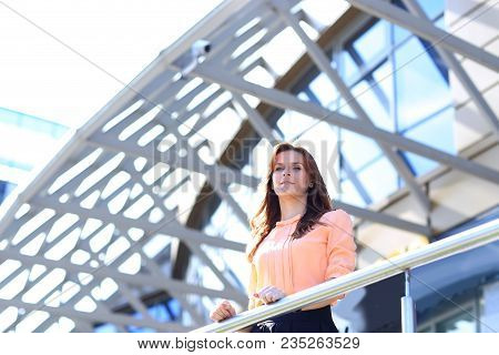 Modern Business Woman Standing On The Balcony Of A Modern Office Building.photo With Copy Space