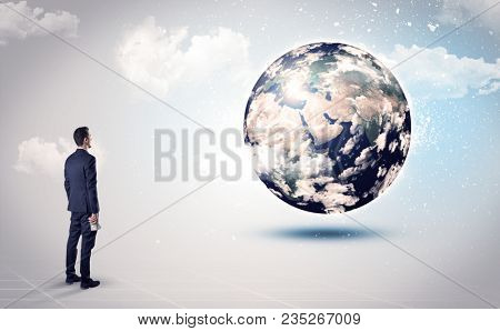 Businessman standing with his back with objects in his hand and looking at the globe, courtesy of NASA
