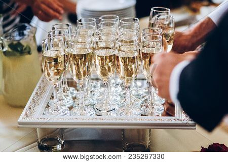 Elegant People Holding Glasses Of Champagne At Luxury Wedding Reception. Hands Taking Drinks And Toa
