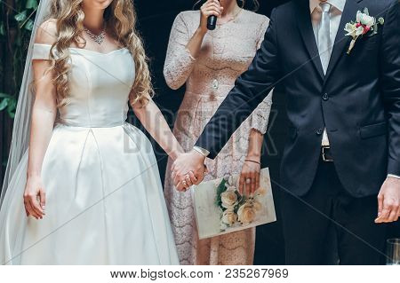 Bride And Groom Holding Hands At Wedding Ceremony Indoors. Ceremony Master Performing Speech