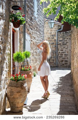 Cute Blonde Tourist Woman In White Dress Walking Home Along The Small Fairy-tale Street With Flowers