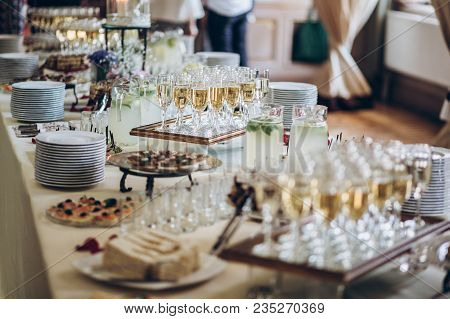 Stylish Champagne Glasses And Food  Appetizers On Table At Wedding Reception. Luxury Catering At Cel