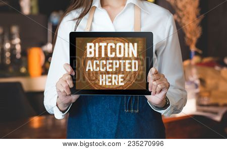 Close Up Woman Barista Holding Tablet And Show Bitcoin Accepted Here On Tablet Screen At Cafe Counte