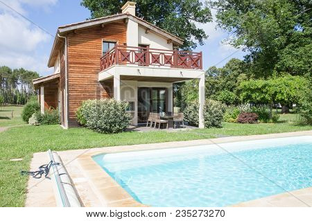 Outdoor Swimming Pool With Large Home In Background With Green Trees