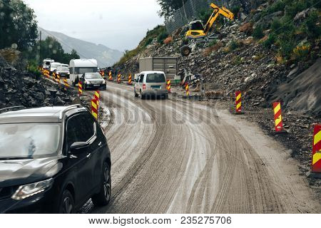 Close-up Passing Road With Civilian Cars Along The Mountain Shoulder Near A Large Rocky Cliff. Along