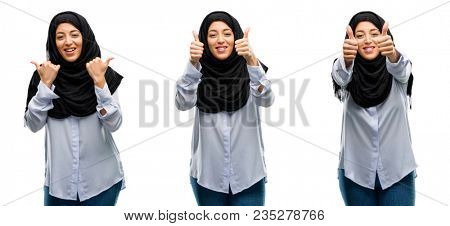 Arab woman wearing hijab smiling broadly showing thumbs up gesture to camera, expression of like and approval isolated over white background