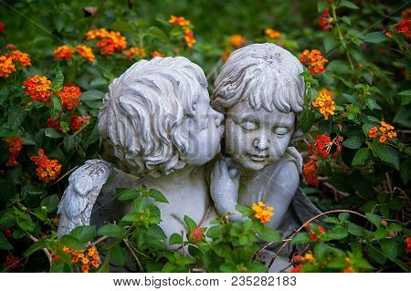 ANGELS IN LOVE. Sculptures of boy and girl angels surrounded with flowers hugging and cuddling. The boy angel is kissing her by the cheek. poster