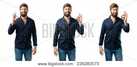 Young man with beard doing ok sign with hand, approve gesture isolated over white background