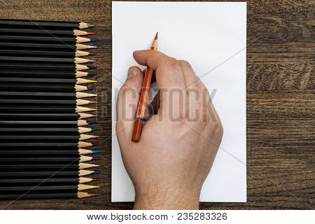 Background Or Background From Pencils. In The Center Is A White Sheet. A Hand Is Holding A Pencil.