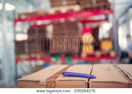 Photo of cardboard boxes with stationery knife