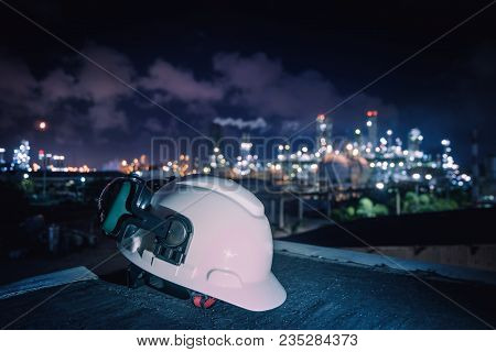 White Safety Helmet And Ear Muff On Industrial Plant Background, Worker Concept In Petrochemical Ind