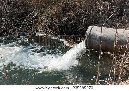 Concrete Pipe Transporting The Poluted River In To A Small Pound.