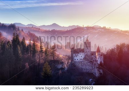 Bran Or Dracula Castle In Transylvania, Romania. The Castle Is Located On Top Of A Mountain, Sunset