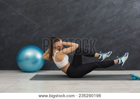 Fitness Woman Working On Her Abs Sitting On Mat At Gym. Young Slim Girl Making Aerobics Exercise. He