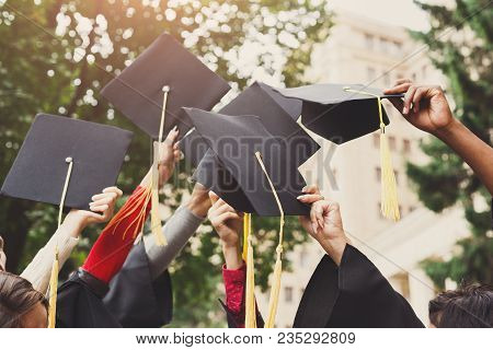 A Group Of Multietnic Students Celebrating Their Graduation By Throwing Caps In The Air Closeup. Edu