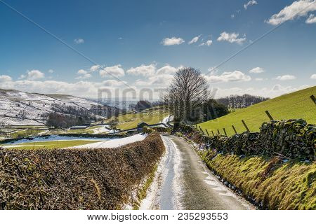 A Country Lane Leading Through Snow Spattered Farmland In Cumbria, Northern England.